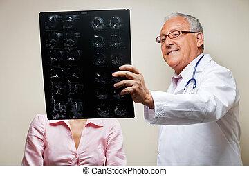 Radiologist Holding X-ray - Senior male radiologist holding...