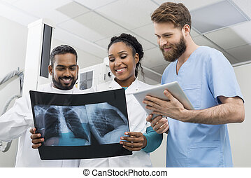 Radiologists With Chest X-ray And Digital Tablet In Hospital