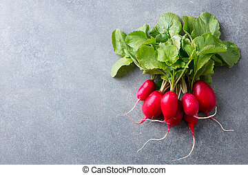 Radish bunch on grey stone background. Copy space. Top view.