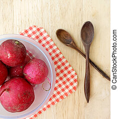 Radish in bowl on wooden table