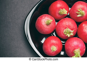Radishes in a black plate