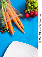 radishes, notebook and carrots with leaves on blue background
