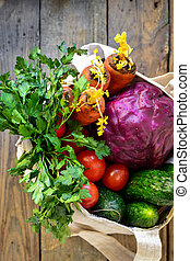 Radishes, tomatoes, cucumbers, carrots, red cabbage in a bag. Wood background. Top view. Fabric bag made of linen.