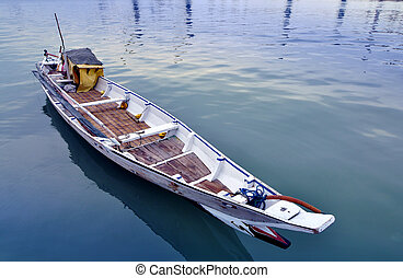 raditional white wooden boat on blue lake