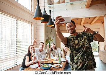 radosny, człowiek, wpływy, selfie, z, jego, przyjaciele, na stole