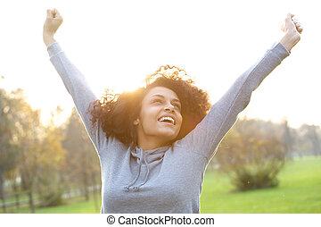 radosny, młoda kobieta, uśmiechanie się, z, herb podniesiony
