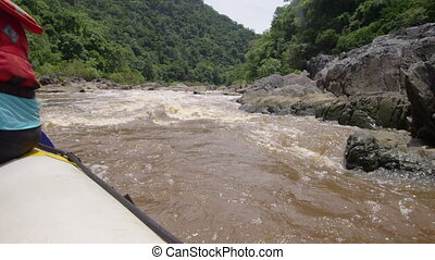 Rafting on a muddy stream - A girl wearing a blue shirt and...