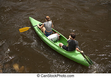 Rafting on wild water - couple in canoe