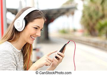 ragazza adolescente, ascolto, a, il, musica, con, cuffie, attesa, uno, treno