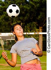 ragazza adolescente, intestazione, palla calcio, mentre, gioco, su, campo