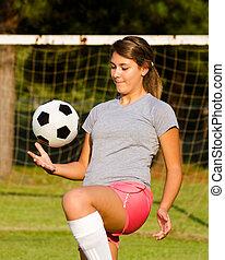 ragazza adolescente, manipolazione, palla calcio, con, lei, ginocchia