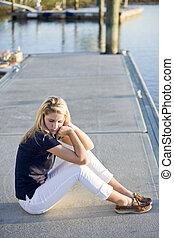 ragazza adolescente, seduta, su, bacino, vicino, acqua