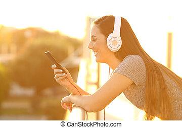 ragazza, ascoltando musica, a, tramonto, in, uno, balcone