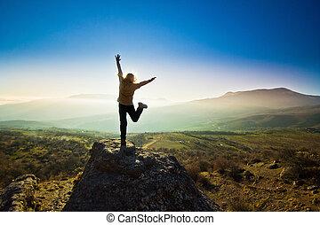 ragazza, con, mani in alto, montagne, contro, sole