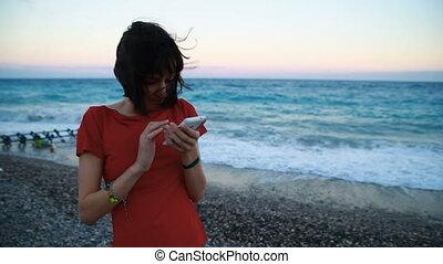 ragazza, con, uno, smartphone, leva piedi, a, il, mare,...