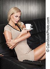 ragazza, cup., lente, attraente, vestire, bere, biondo, il portare, divano, giovane, occhi pesti, corto, incantando, sexy, è, dall'aspetto, ha, attraversato, arms., seduta