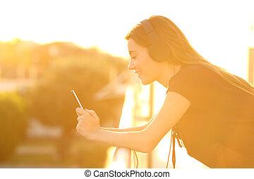 ragazza, usando, uno, far male, telefono, in, uno, balcone, a, tramonto