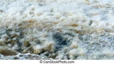 raging stream and the waterfall dam of the hydroelectric...