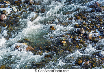 Raging water breaker among icy rocks with frazil of mountain river in winter