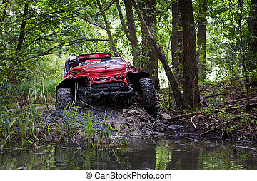 a red car driving through the mad and water