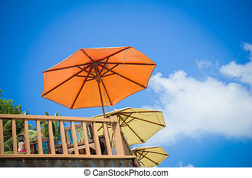 Rail fence and umbrellas on the sky background