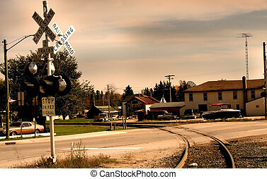 Rail road crossing near small village in sepia color tone