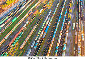 Rail sorting freight station with various railway cars, with many rail tracks railroad. Aerial view heavy industry landscape.