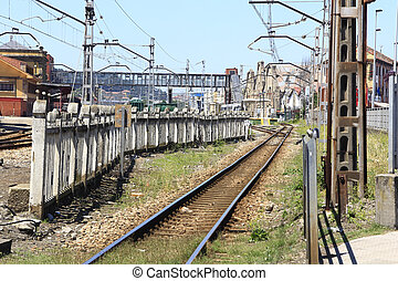rail train entering a station, with many utility poles