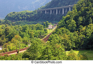Railroad and new road in Swiss Alps, Europe.