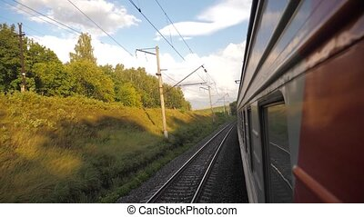 Railroad cars outside train ride on rails near the forest railway. slow motion video. The train with the carriages moves next to the forest. concept lifestyle railroad train cars and train journey travel