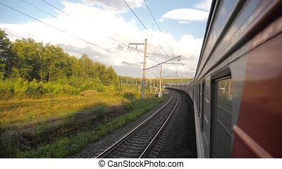 Railroad cars outside train ride on rails near the forest railway. slow motion video. The train with the carriages moves next to lifestyle the forest. concept railroad train cars and train journey travel