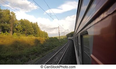Railroad cars outside train ride on rails near the forest railway. slow motion video. The train with the carriages moves next to the forest. lifestyle concept railroad train cars and train journey travel