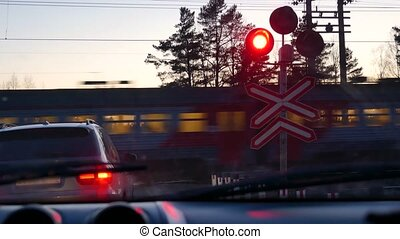 A passing train at a railway crossing.