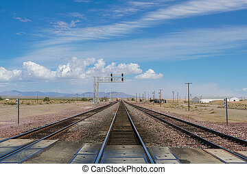 Railroad crossing gates on a road in the Mojave Desert
