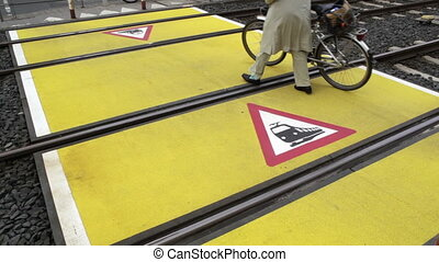 Railroad crossing - Pedestrian with a bike walks over the...