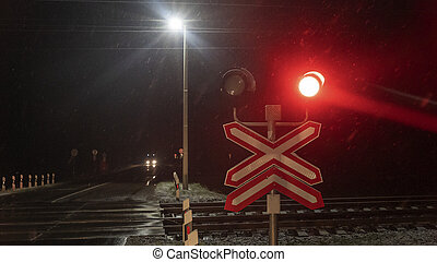 Railroad crossing with passing train by night. Train crossing gates closed on rural road at late evening. Drops of rain. Road sing concept.