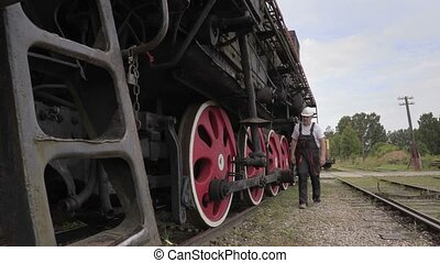 Railroad employee checks the locomotive