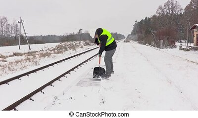 Railroad employee clean snow near railway and walking away