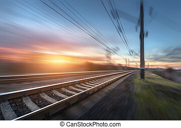 Railroad in motion at sunset. Railway station