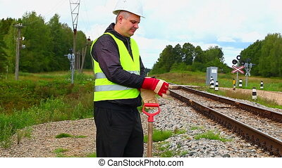 Railroad maintenance worker with showel