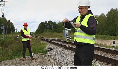 Railroad maintenance workers with rope and with shovel