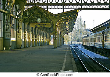 """Railroad station platform with a hanging clock and """"Have a ..."""