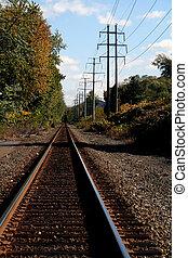 Railroad Tracks - Train tracks under autumn sky in rural...