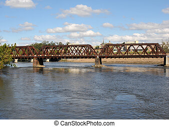 Railroad bridge in Shelton, Connecticut, under a blue sky on a fall day