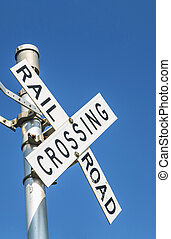 Railroad warning crossing sign under blue sky