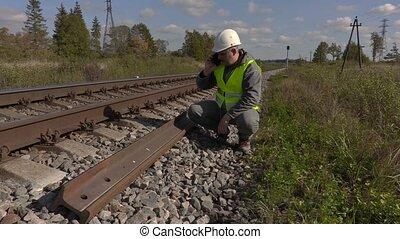 Railroad worker talking on smart phone near the rails