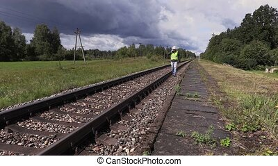 Railroad worker with adjustable wrench walking near railway