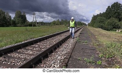 Railroad worker with cell phone and adjustable wrench...