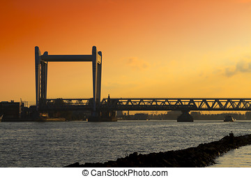 Railway bridge in Dordrecht at sunset with a dramatic sky -...