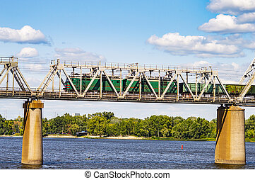 Railway bridge over the river with a train against a blue sky.